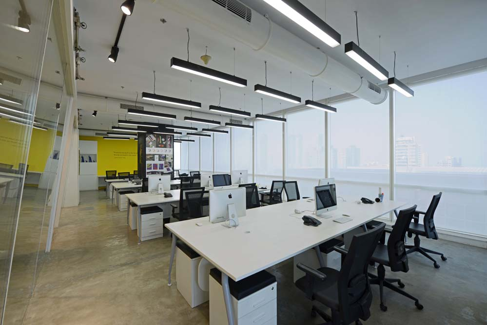 View of the open office. The cement flooring contrasts with the inclined glass partition.