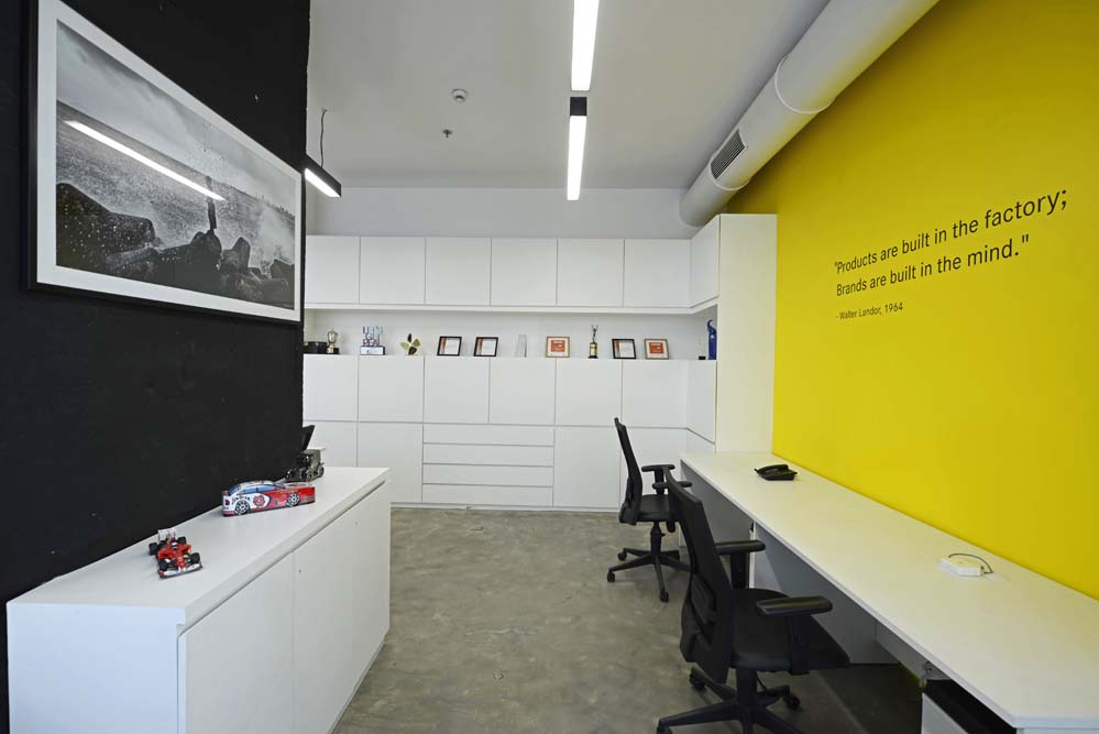 A niche allows for display of awards and trophies; whilst a yellow wall highlights a quote by the company's founder.